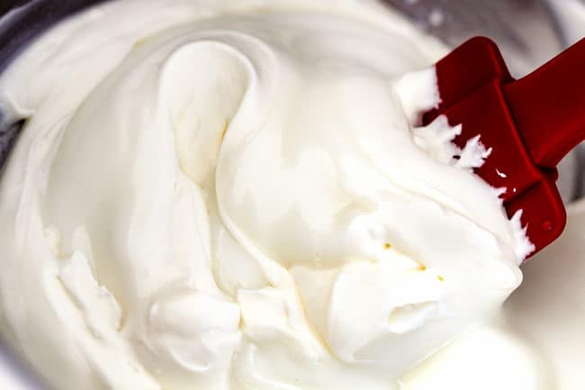 showing how to make ambrosia salad by mixing yogurt and cream together