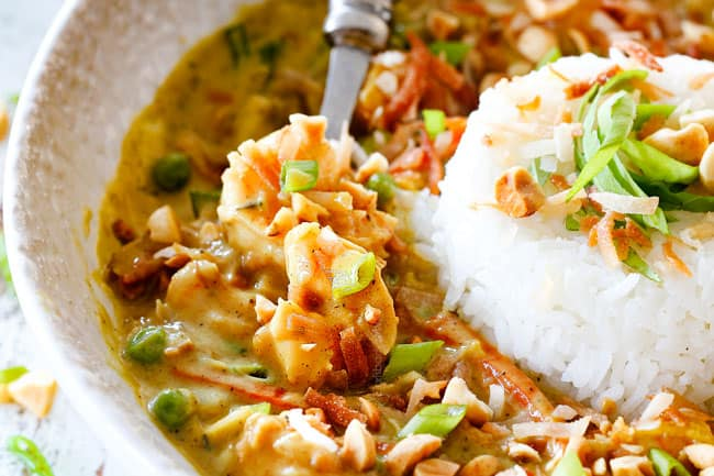 up close side view of Copycat Bang Bang Shrimp with rice and coconut in a white bowl with zucchini, peas and carrots