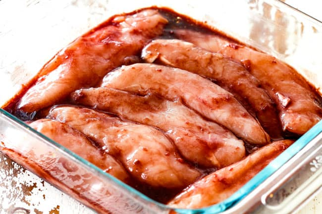 showing how to make hoisin chicken by marinating chicken in hoisin marinade in a glass dish