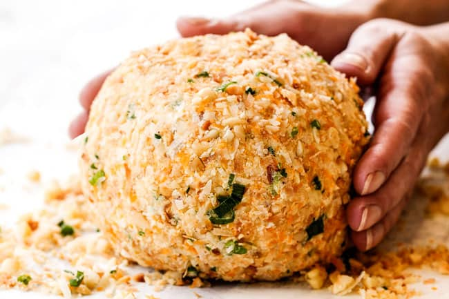 showing how to make Pineapple Cheese Ball by rolling in coating with macadamia nuts, coconut and green oninos