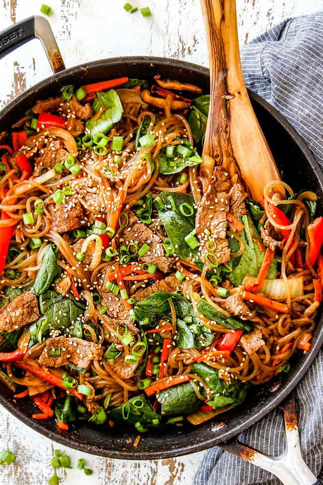 top view of spicy Korean noodles with cellophane noodles, steak, mushrooms, carrots, onions, garlic