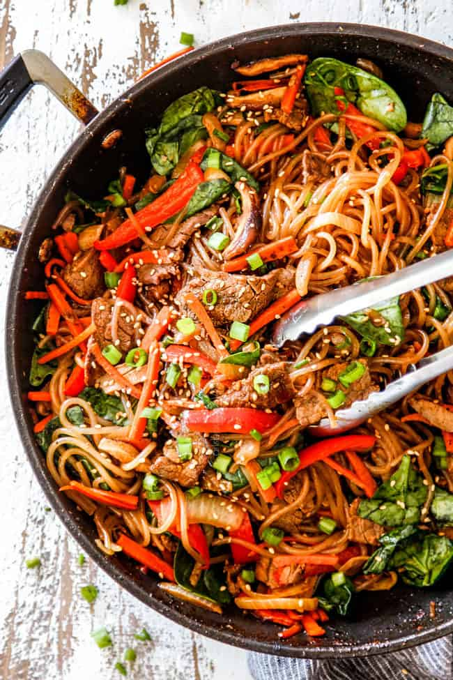 top view of spicy Korean noodles with tongs grabbing glass noodles, steak and vegetables