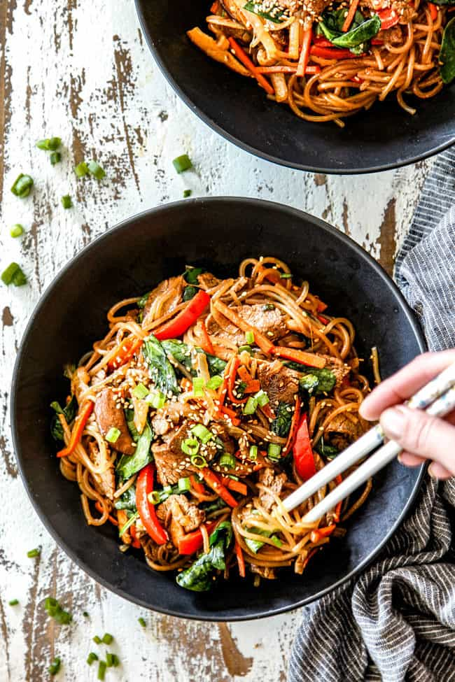 top view Korean fire noodles in a black bowl with chopsticks