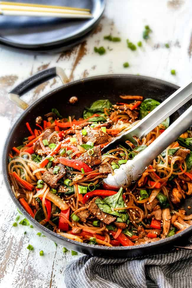 far away view of a pair of tongs grabbing a bite of Spicy Korean Noodles with steak, shiitake mushrooms, carrots, spinach