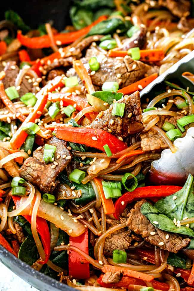 up close of a pair of tongs grabbing a bite of Spicy Korean Noodles