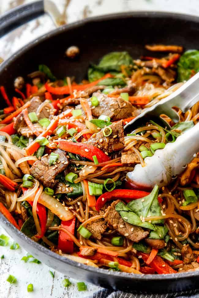 a pair of tongs grabbing a bite of Spicy Korean Noodles with glass noodles