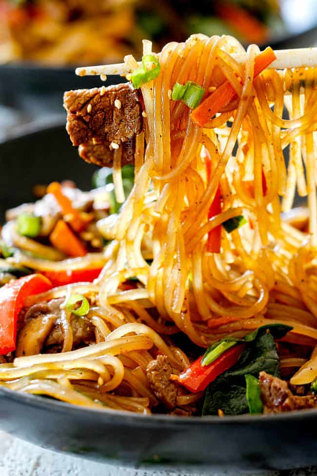 a pair of chopsticks holding up Spicy Korean Noodles with steak