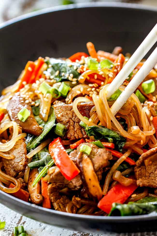 a bowl of Korean Spicy Noodles with beef, mushrooms, carrots, sesame seeds, green onions with white chopsticks