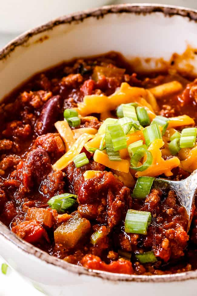 a spoonful of the best turkey chili with green onions and cheese