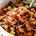seasoned wild rice recipe with a spoon raising rice out of the bowl
