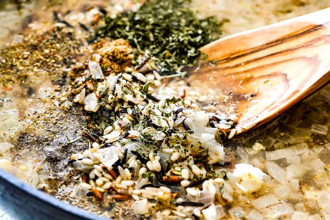showing how to cook flavorful wild rice by adding wild rice, seasonings, herbs, onions and garlic to a saucepan
