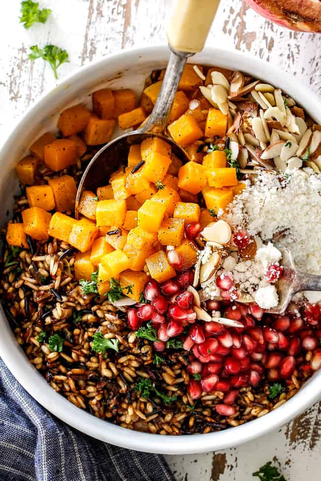 showing how to make wild rice recipe side dish by adding wild rice, squash and pomegrantes to a white bowl