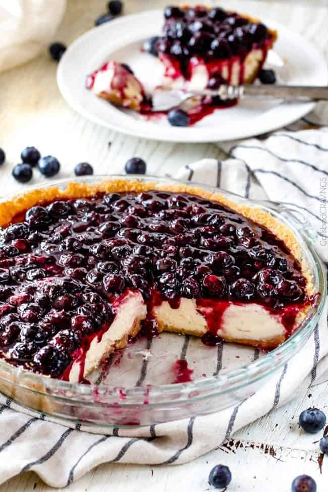 easy blueberry cheesecake recipe with fresh blueberries on a table with slices missing