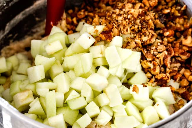 showing how to make poke cake by adding apples and walnuts to a bowl