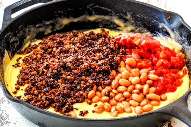 showing how to make Queso Fundido by adding chorizo, beans and tomatoes to melted cheese