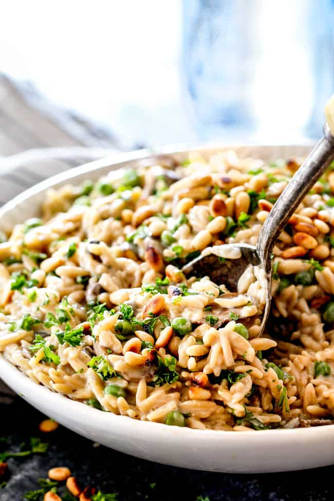 side view of cheesy orzo pasta recipe with a serving spoon with mushrooms and peas