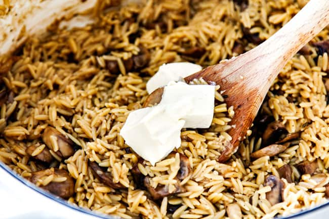 showing how to make creamy orzo pasta by stirring in cream cheese