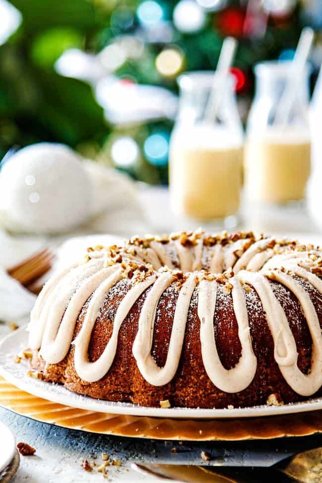 far away view of easy eggnog bundt cake with eggnog frosting with a christmas tree with lights in the background