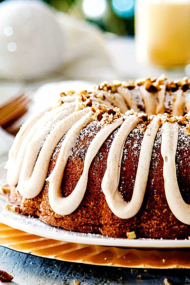front view of eggnog cake bundt recipe garnished with pecans with cups of eggnog in the background