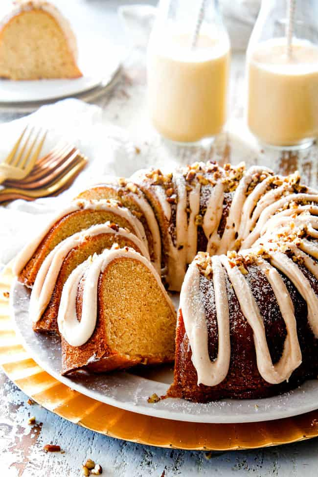 holiday eggnog cake on a white platter with two slices cut out