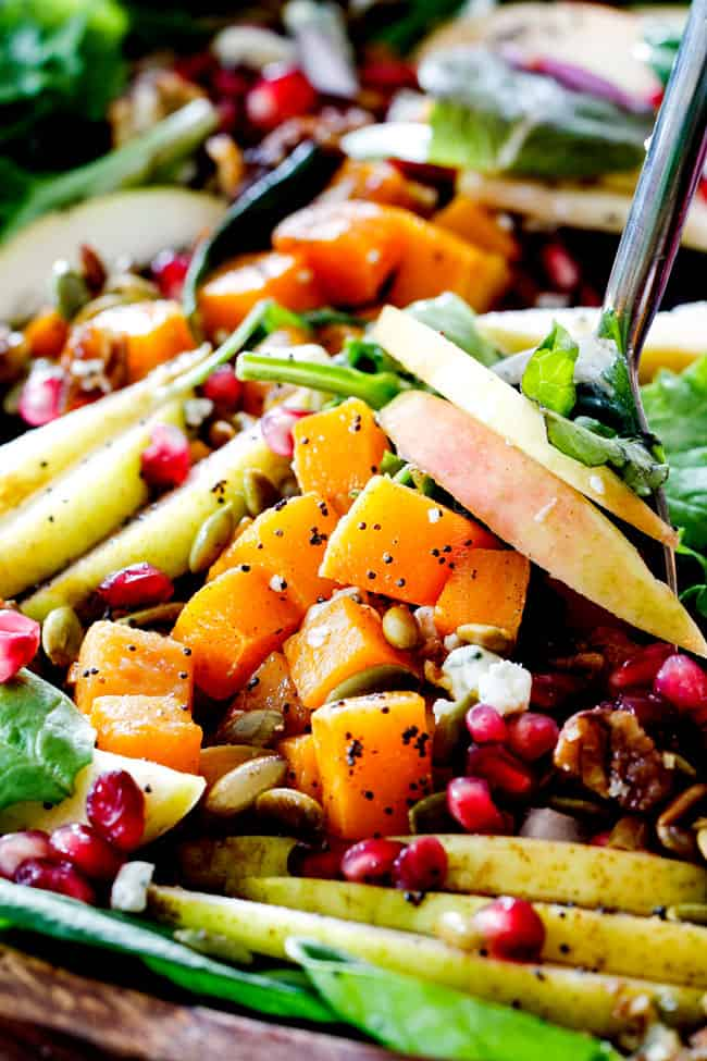 tossing Fall Salad with tongs that has pears and apples, pecans
