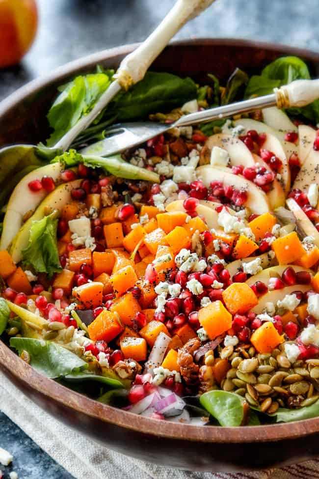 side view of fresh fall salad in large wood bowl with pecans, pears, apples, squash, dried cranberries, butternut squash, gorgonzola cheese