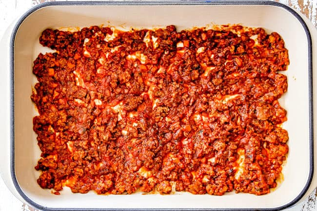 showing how to layer lasagna with a layer of meat sauce on the bottom of the pan