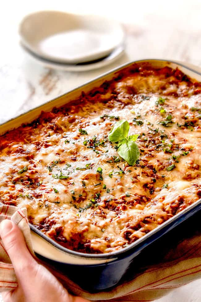 two hands holding a pan of traditional lasagna in a blue dish