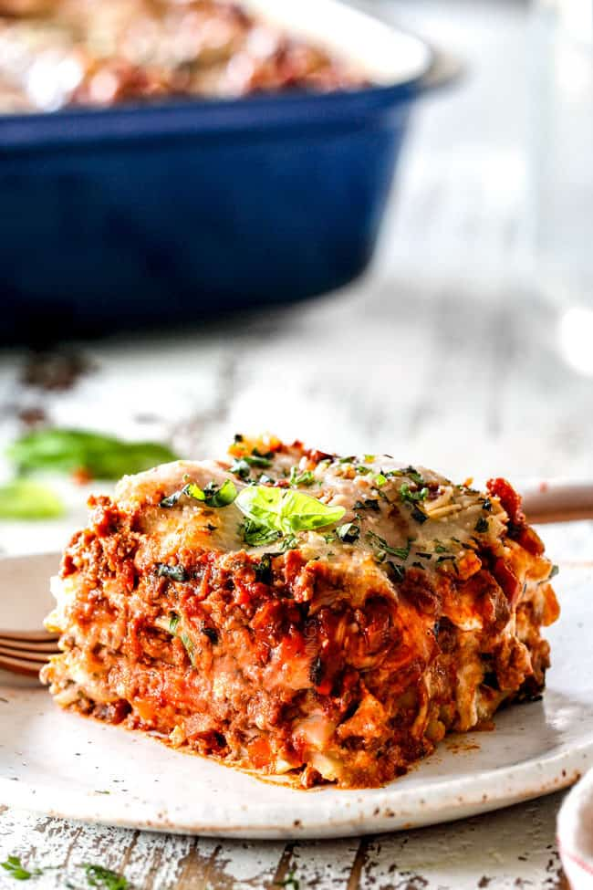 a slice of traditional lasagna with layers of ricotta, noodles, meat sauce, mozzarella, Parmesan with fresh parsley garnish on a white plate