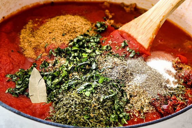 showing how to make traditional lasagna by making homemade Bolognese by adding tomato sauce, crushed tomatoes, tomato paste, fresh basil, parsley, and oregano to a pot