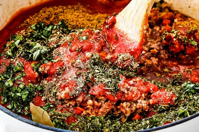 showing how to make best lasagna by making stirring homemade meat sauce with crushed tomatoes, tomato sauce, tomato paste, fresh basil, parsley, and oregano to a pot