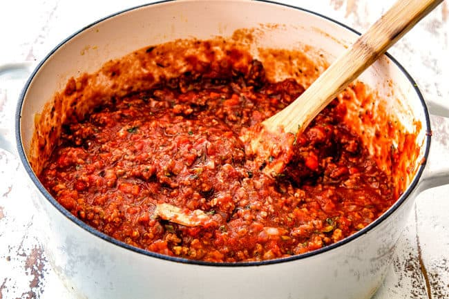 showing how to make easy lasagna by simmering homemade meat sauce in a white Dutch oven