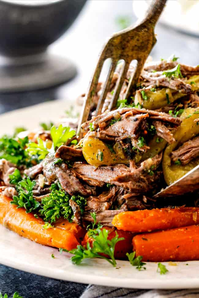 tongs taking a serving of Mississippi Pot Roast with potatoes and carrots from white platter