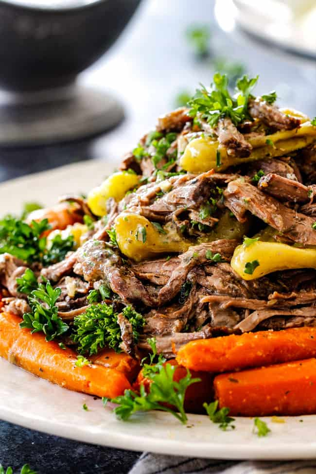 up close of best Crockpot Mississippi Pot Roast on a white platter with carrots
