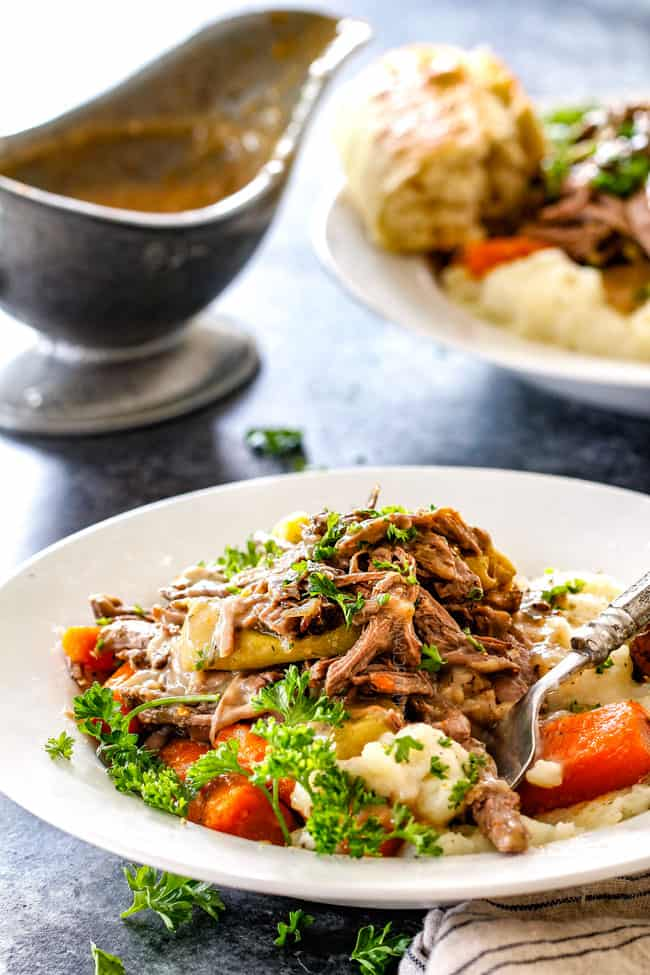 a serving of easy Mississippi Pot Roast with potatoes and carrots with gravy