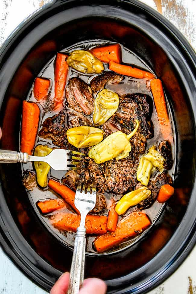 showing how to make Mississippi Pot Roast in crock pot by shredding chuck roast