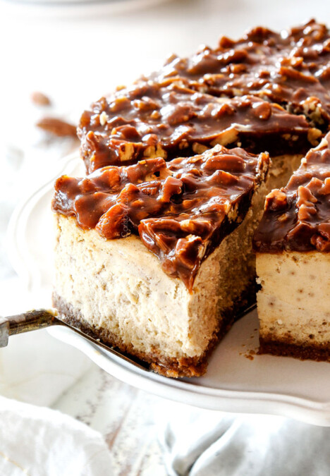 up close taking a slice of pecan pie cheesecake with graham cracker crust on a pedestal