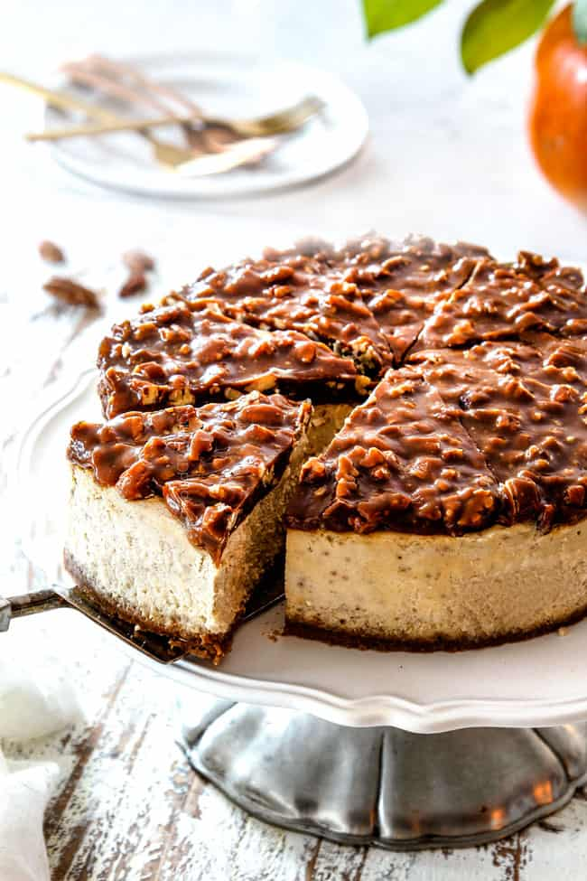 taking a slice of easy pecan pie cheesecake on a pedestal