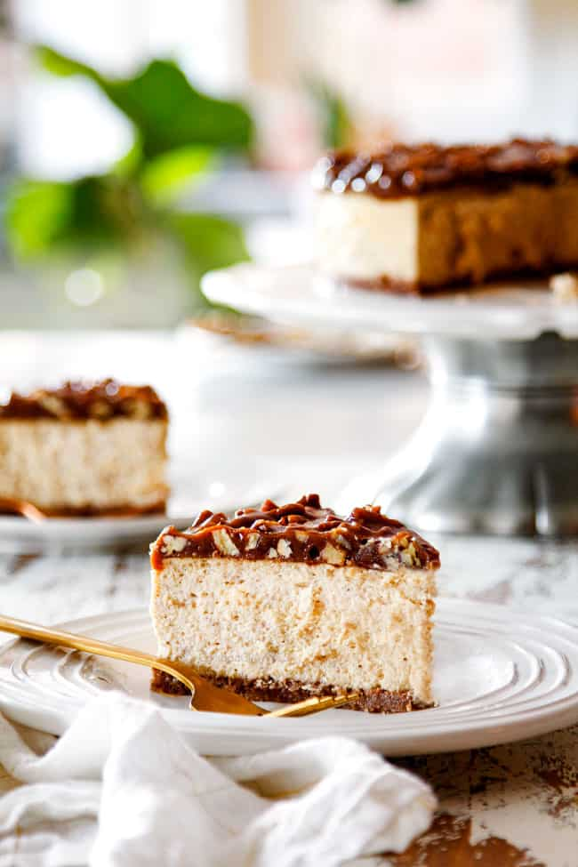 far away view of side view of a slice of best pecan pie cheesecake on a white plate with a gold fork with the whole cheesecake on a pedestal