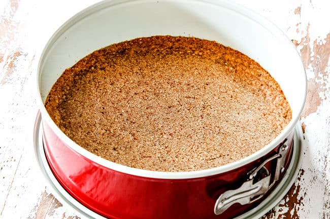 showing how to make easy pecan pie cheesecake by baking graham cracker crust in a springform pan