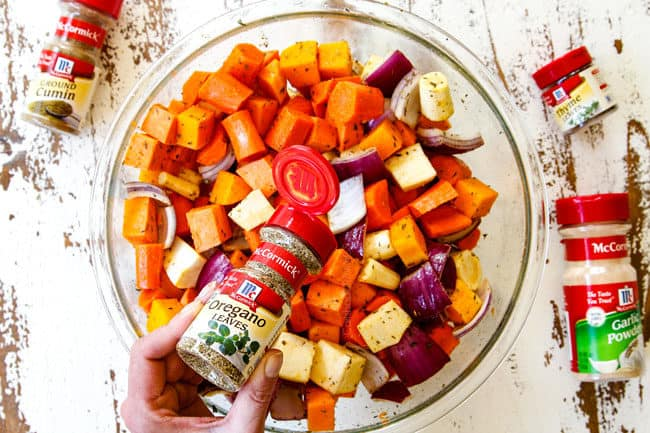 showing how to make roasted root vegetables by adding rosemary, thyme, oregano, parsley to a bowl with vegetables
