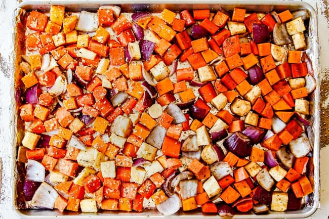 showing how to make oven roasted root vegetables by spreading them out evenly on a baking sheet