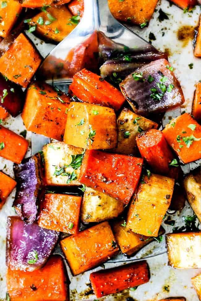 top view of a spatula full of oven roasted root vegetables on a baking sheet