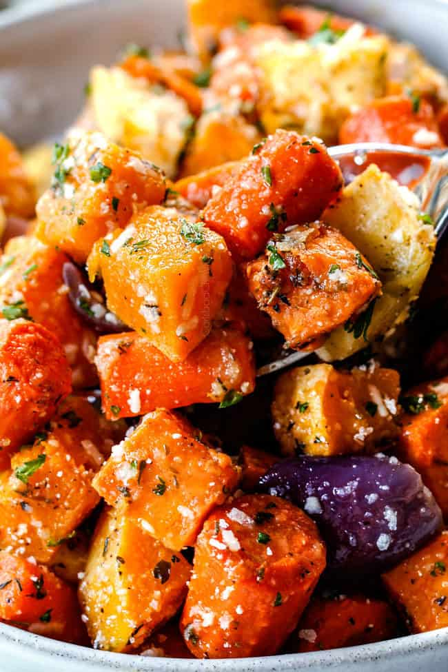 close up view of a spoonful of roasted root vegetables with butter, garlic and parmesan