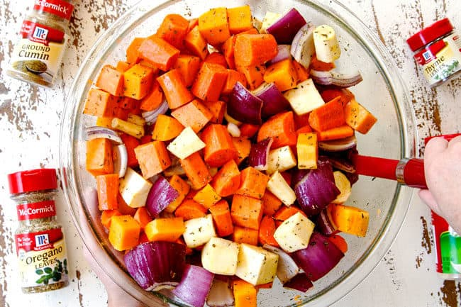 showing how to make roasted root vegetables b adding chopped carrots, sweet potatoes, parsnips, butternut squash and onions to a glass bowl