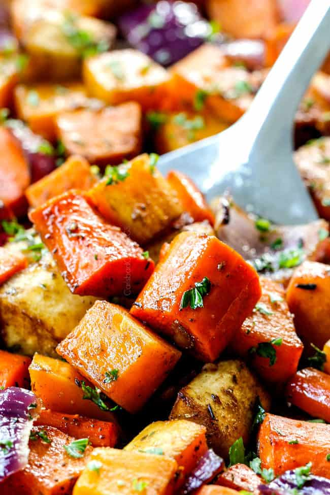up close of a spatula scooping up balsamic roasted root vegetables with garlic on a baking tray