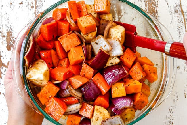 showing how to make roasted root vegetables with balsamic by stirring the vegetables and balsamic together in a glass bowl