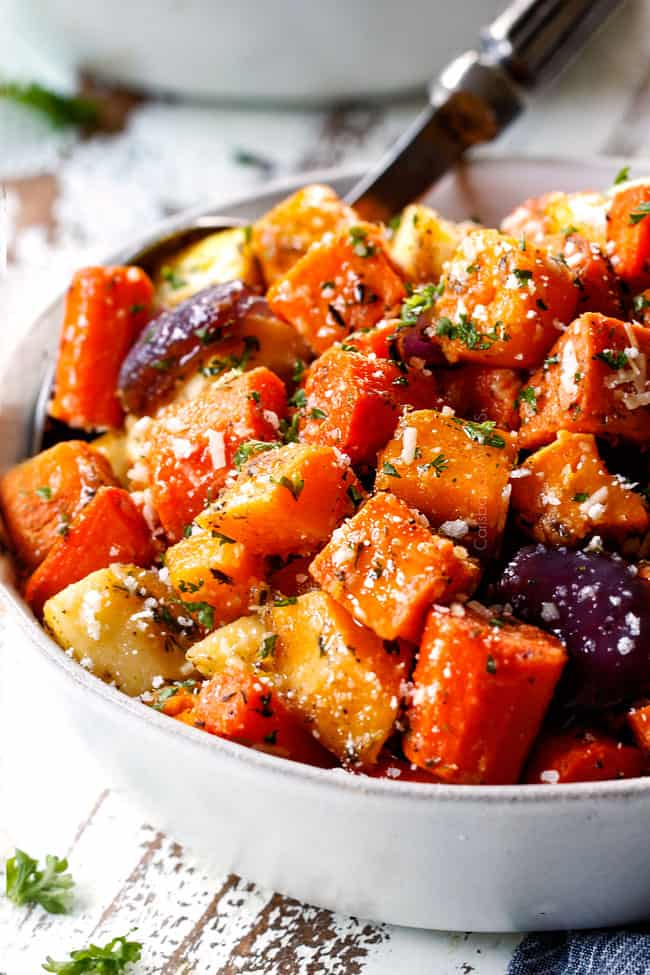 side view of a bowl of roasted root vegetables with garlic and Parmesan