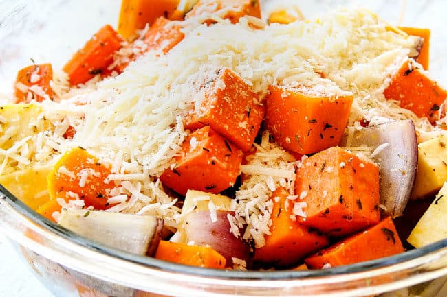 showing how to make oven roasted root vegetables by adding Parmesan to vegetables in a glass bowl