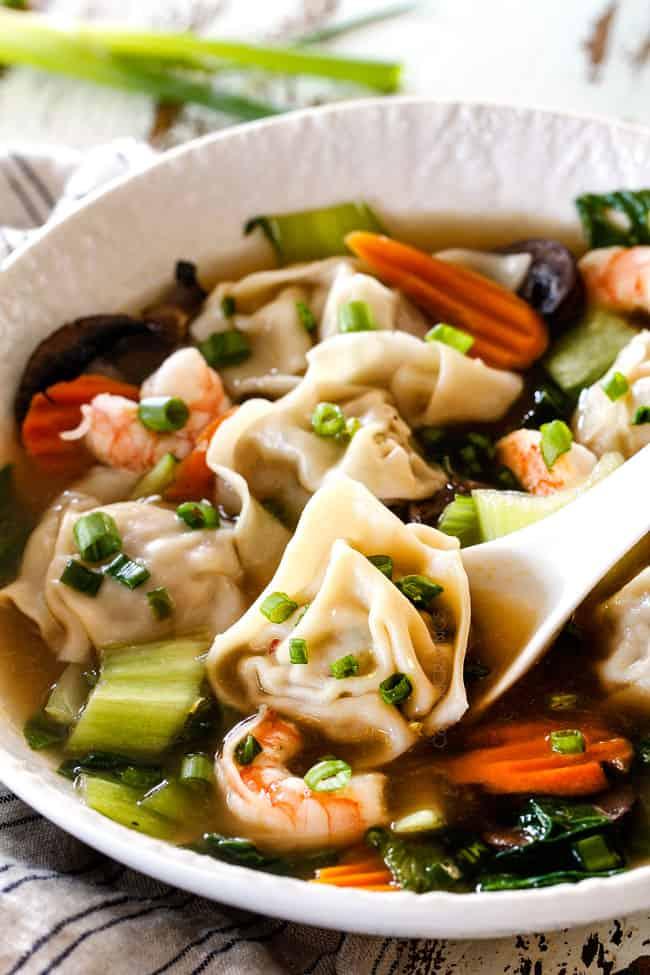 spooning a wonton in easy wonton soup recipe